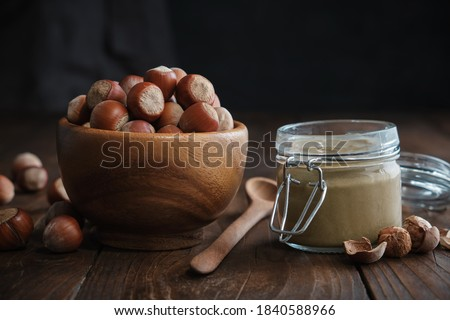Wooden bowl of hazelnuts, glass jar of raw organic hazelnut butter or paste on kitchen table.  Foto d'archivio ©