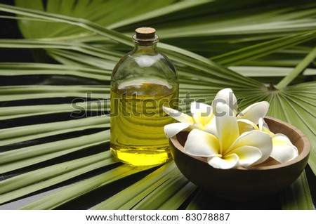 Wooden bowl of plumeria on and spoon on palm leaf texture