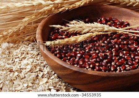 Wooden bowl of red corn kernels with wheat spikes and oat flakes.  Macro with shallow dof. - stock photo