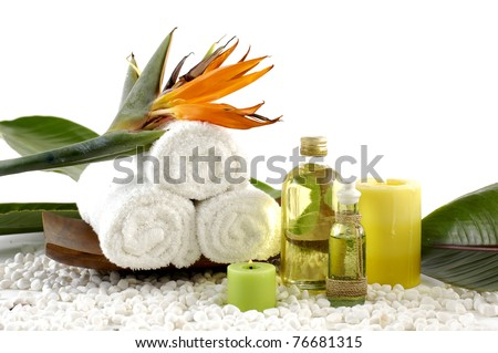 wooden bowl of towel and spring flower with massage oil on white pebble