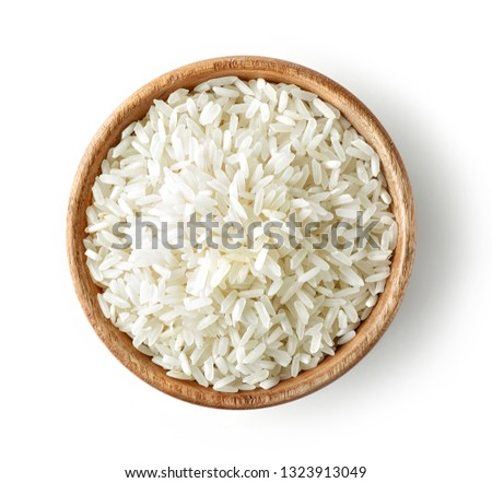 wooden bowl of uncooked rice isolated on white background, top view