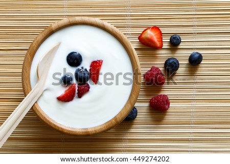 Wooden bowl of white yogurt with wooden spoon inside on bamboo matt from above. Next to berries. #449274202