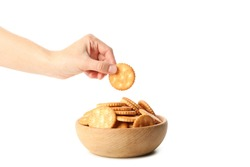 Wooden bowl with cracker biscuits and female hand holds cracker, isolated on white background