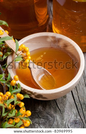 Wooden bowl with fresh honey and orange berries on old wooden table