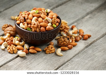 Wooden bowl with mixed nuts on a wooden gray background. Healthy food and snacks, organic vegetarian meals. Walnut, pistachios, almonds, hazelnuts and cashews, walnut. #1233028156