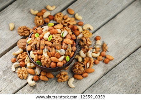 Wooden bowl with mixed nuts on a wooden gray background. Healthy food and snacks, organic vegetarian meals. Walnut, pistachios, almonds, hazelnuts and cashews, walnut. #1255910359