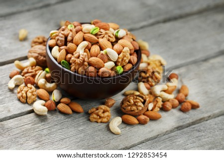 Wooden bowl with mixed nuts on a wooden gray background. Walnut, pistachios, almonds, hazelnuts and cashews, walnut. #1292853454
