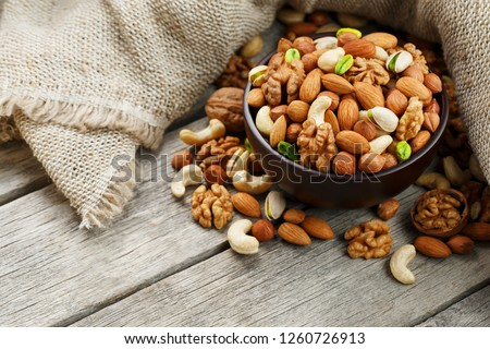 Wooden bowl with nuts on a wooden background, near a bag from burlap. Healthy food and snack, organic vegetarian food. Walnut, pistachios, almonds, hazelnuts and nuts of cashew, walnut. Top view. #1260726913