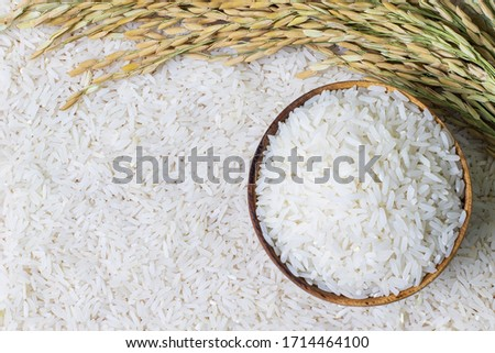 Wooden bowl with rice on rice and rice ears background with copy space for your text, top view. Natural food high in protein