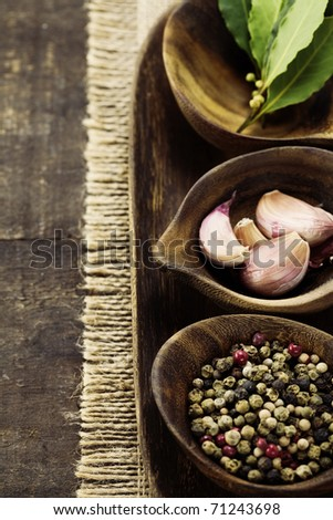 wooden bowls with fresh herbs and spices ( garlic, pepper, bay leaves)