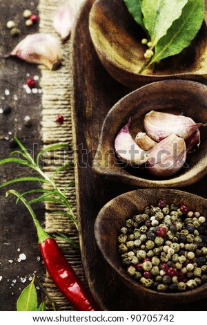 wooden bowls with fresh herbs and spices ( garlic, pepper, bay leaves, salt)