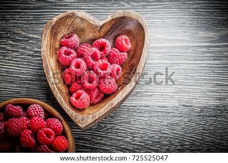 Wooden bowls with ripe raspberries on wood board. #725525047