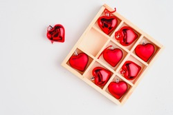 Wooden box filled with heart shaped christmas ball, isolated on white, top view