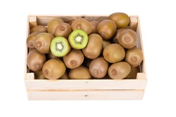 Wooden box filled with many ripe and fresh kiwi fruits and two half fruits isolated on white background