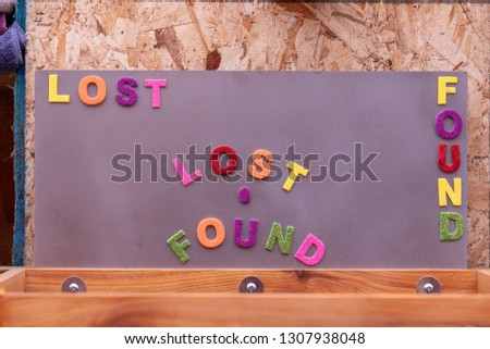 """Wooden box for lost items with """"Lost and Found"""" title above it. The title made from glittering foam letters #1307938048"""