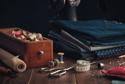 Wooden box of spools of thread, stack of fabrics and sewing items - tailoring scissors, cutting knife, paper for sewing pattern, measuring tape, thimble, cushion for including pins and needles.