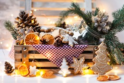 Wooden box with delicious homemade gingerbread cookies with white icing. Perfect beautiful gift in rustic style. Orange, cones, fir tree branches and lights as decor. Close up. Cozy home atmosphere