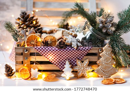 Photo of  Wooden box with delicious homemade gingerbread cookies with white icing. Perfect beautiful gift in rustic style. Orange, cones, fir tree branches and lights as decor. Close up. Cozy home atmosphere