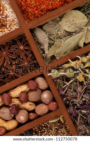 Wooden Box with Mixed Spicy Spices, Herbs and Dried Leafs close up