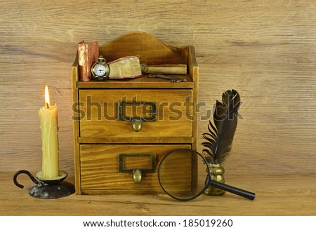 Wooden box with old written implements and burning candle #185019260