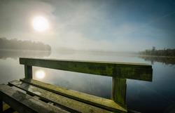 Wooden bridge and spider web at sunrise