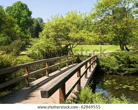 Wooden bridge in green garden in the afternoon