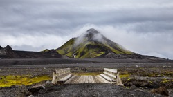 Wooden bridge in Iceland on hill background with cloudy sky