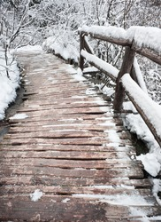 Wooden bridge in snow close-up. Winter forest of Plitvice national park, Croatia.