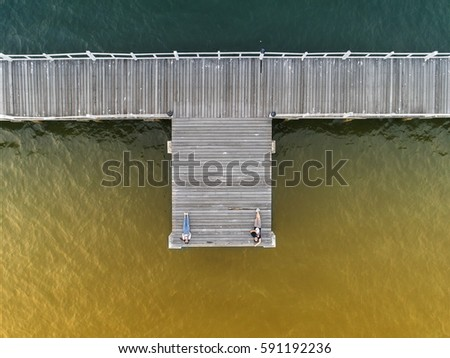 wooden bridge laying into lake at sunset shade in aerial view