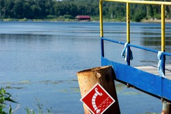 Wooden bridge on the lake shore, water intake sign for fire engines on a specialized pipe