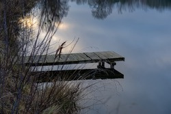 Wooden bridge on the river bank in the evening. Winter season.