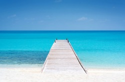 Wooden bridge or pier on tropical white sand beach with clear blue sea and sky on sunny day. Boardwalk into the ocean and turquoise water. Summer holidays background with copy space. Kuramathi Island.