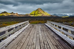 Wooden bridge over a river in ICELAND. Beautiful Icelandic landscape with mountains, sky and clouds. Trekking in national park Landmannalaugar