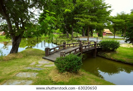 Wooden bridge over little river in city park