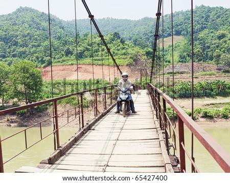 Wooden bridge over mountain river. Northern Vietnam