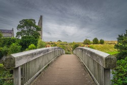 Wooden bridge over River Boyne with a view on ruined tower of St. Marys Abbey near Trim castle, County Meath, Ireland
