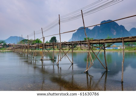 Wooden bridge over river song to riverside guesthouse for Domon river guesthouse vang vieng