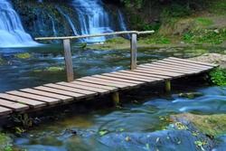Wooden bridge over river stream