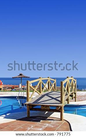 Wooden bridge over swimming pool in Spanish urbanisation with stunning sea views - stock photo