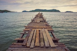 Wooden bridge pier leading to the sea, copy space, vintage toned
