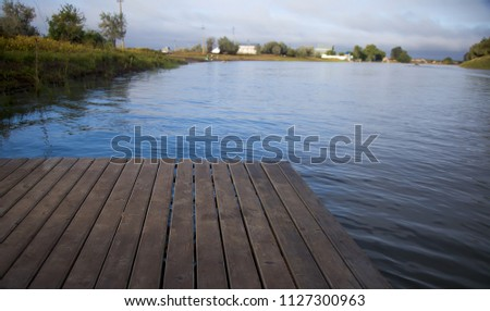 Wooden bridge, pier near the river, bridge, pier, wooden. A natural blurred landscape of the river in summer at sunset. Astrakhan Region, Russia #1127300963