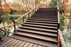 Wooden bridge stairs. Walking around famous West Lake park in Hangzhou city center, China. Vintage toned photo with Instagram filter effect