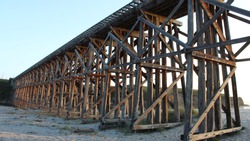 Wooden bridge walkway on the sandy beach at sunset. solid rustic structure ancient wooden beams