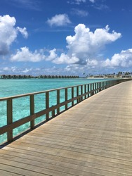 Wooden bridge with turquoise blue ocean,water villas,blue sky and clouds in the background in Maldives