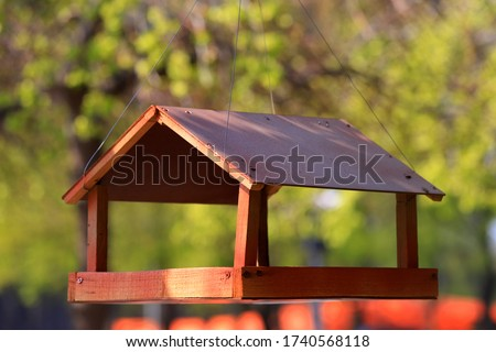 Wooden brown birdhouse, manger hanging on a tree in a spring park. Wild Bird Care, Home, and Food. Bird nest in spring Stock photo ©