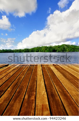 Wooden brown boardwalk on a lake with blue sky and clouds