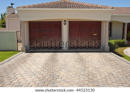 Wooden brown double garage doors of a big house with the drive way in the foreground