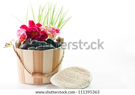Wooden bucket with hot black stones for a massage. In front of the bucket there is a vegetable sponge.
