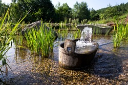 Wooden bucket with oxygenating flowing water at natural swimming pond or pool purifying water without chemicals through biological filters and plants