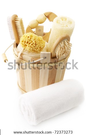 Wooden bucket with SPA accessories isolated on white background.
